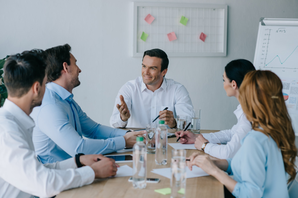 Group of business professionals sitting around a conference table.